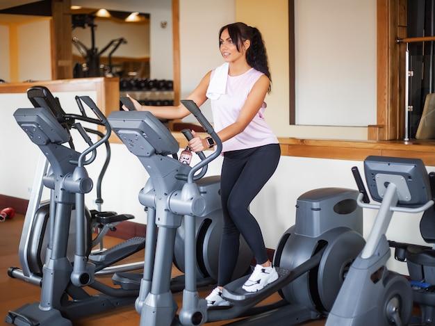 Mulher nova da aptidão que elabora na ginástica. mulher malhando na bicicleta ergométrica
