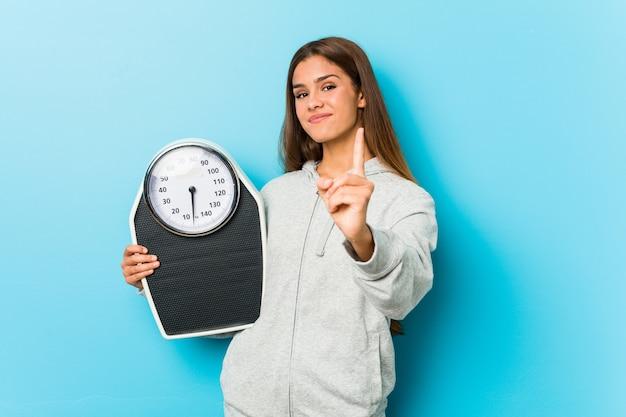 Mulher nova da aptidão que guarda uma escala que mostra o número um com dedo.