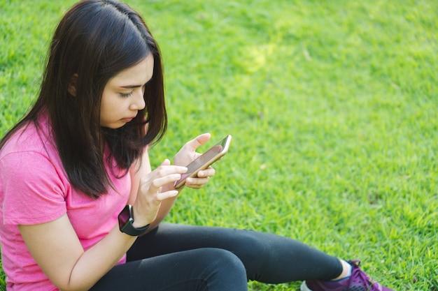 Mulher nova da aptidão que usa o telefone esperto para verificar o progresso do seguimento do app do esporte no parque.