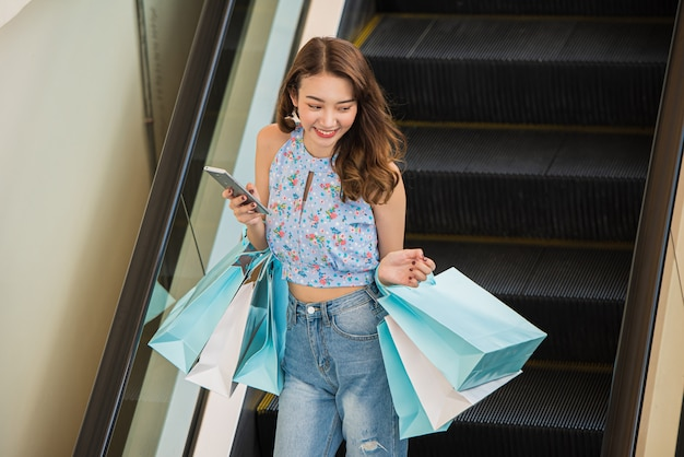 Mulher nova da compra que guarda sacos de papel no shopping, conceito de compra de viagem.