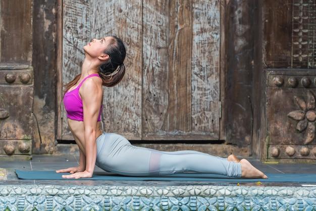 Mulher nova da ioga do esporte que faz o exercício em casa.