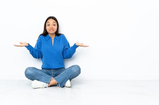 Mulher nova da raça misturada que senta-se no assoalho isolado na parede branca que tem dúvidas ao levantar as mãos