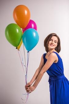 Mulher nova de sorriso da beleza que guarda balões coloridos.