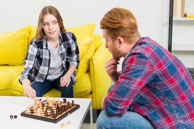 Mulher nova de sorriso que joga o xadrez com seu noivo que olha se