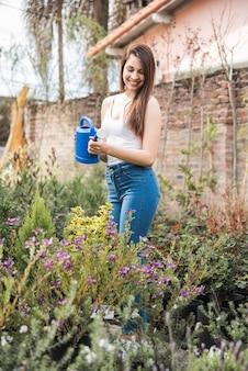 Mulher nova de sorriso que molha as plantas no jardim