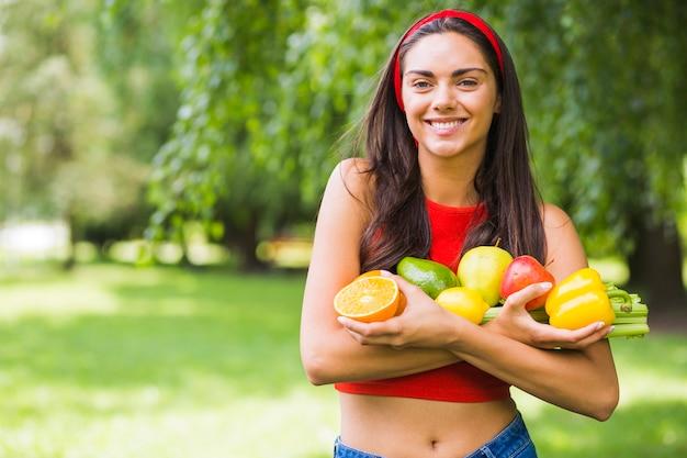 Mulher nova de sorriso que prende legumes frescos e frutas nas mãos