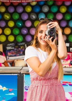 Mulher nova de sorriso que toma retratos com a câmera no parque de diversões