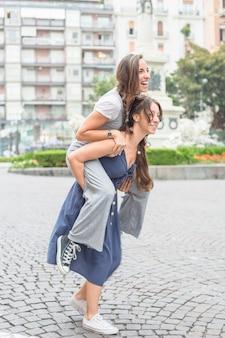 Mulher nova de sorriso que toma seu passeio do sobreposto da amiga na rua