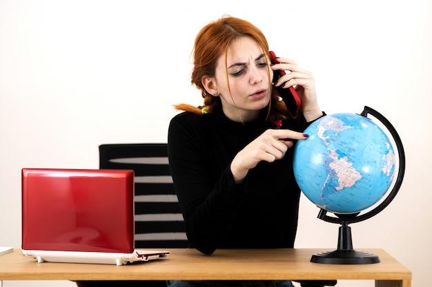 Mulher nova do agente de viagens que senta-se atrás da mesa de trabalho com laptop e globo geográfico do mundo que fala em um telefone celular.