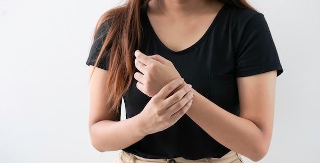 Mulher nova do escritório que sofre da dor da mão no fundo branco.