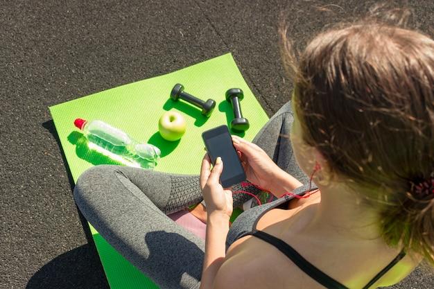 Mulher nova do esporte no estádio usando o smartphone.