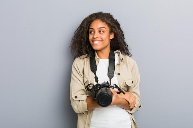 Mulher nova do fotógrafo do americano africano que mantém um sorriso da câmera seguro com braços cruzados.