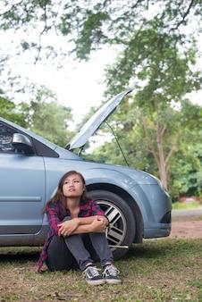 Mulher nova do hipster que espera o auxílio da borda da estrada após seu carro quebra para baixo no lado da estrada que senta-se de encontro a seu carro.