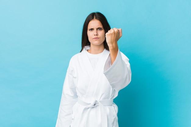 Mulher nova do karaté que mostra o punho à câmera, expressão facial agressiva.