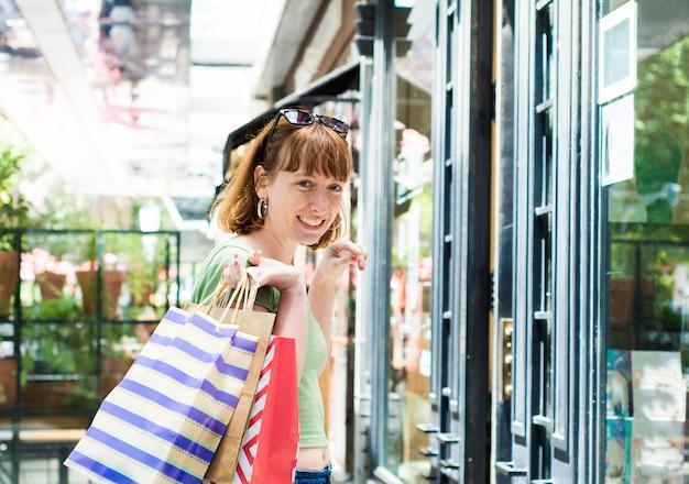 Mulher nova do ruivo com os sacos de compras na cidade.