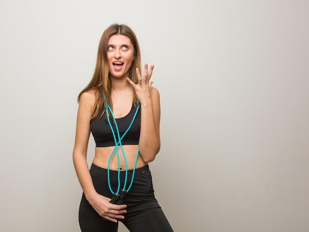 Mulher nova do russo da aptidão irritada e virada. segurando uma corda de pular.