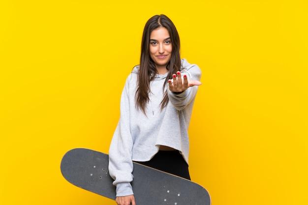 Mulher nova do skatista sobre a parede amarela isolada que convida a vir com mão. feliz que você veio