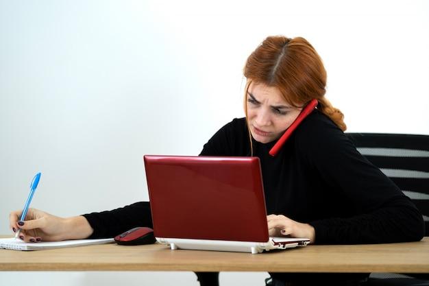 Mulher nova do trabalhador de escritório que fala em um telefone celular que senta-se atrás da mesa de trabalho com laptop e caderno.