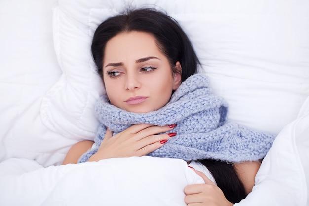 Mulher nova doente que está tossindo na cama