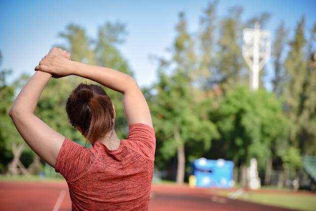 Mulher nova dos esportes que estica seus braços na trilha do estádio antes de correr.
