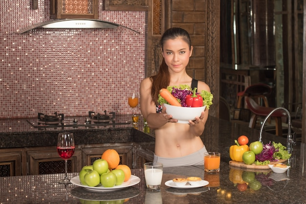 Mulher nova e bonita que está na cozinha com os vegetais nas mãos.