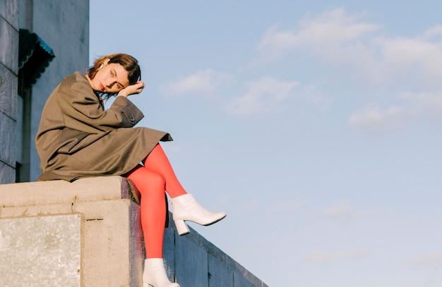 Mulher nova entediada contemplada que senta-se na parede contra o azul manhoso