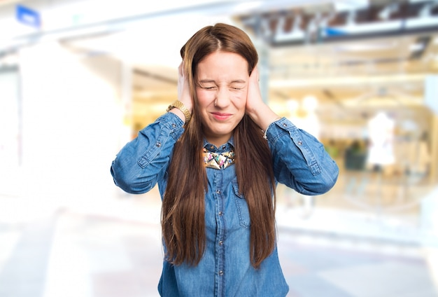 Mulher nova na moda olhando irritado porque um ruído