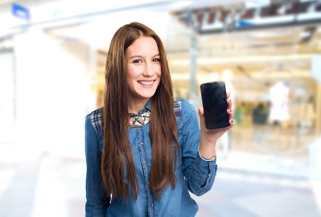 Mulher nova na moda que mostra um telefone inteligente
