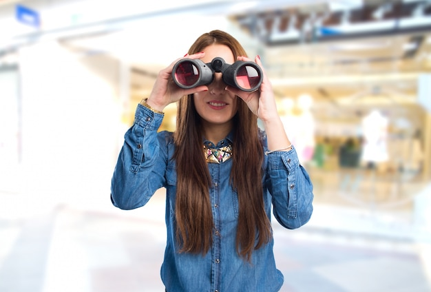 Mulher nova na moda que usa binóculos