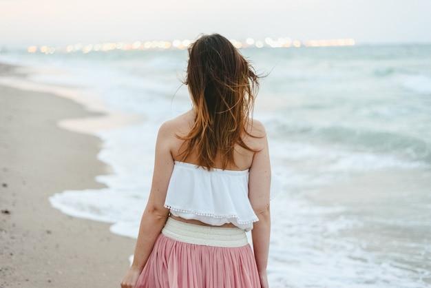 Mulher nova nela para trás na praia que anda só e triste.