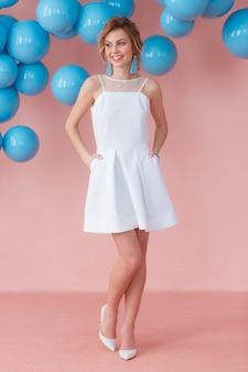 Mulher nova no vestido de cocktail branco que levanta no fundo da parede cor-de-rosa
