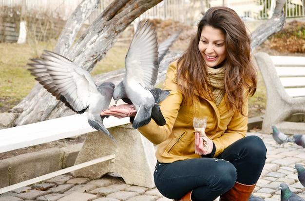 Mulher nova que alimenta pombos felizes