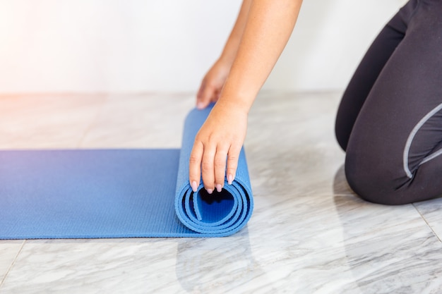 Mulher nova que dobra a esteira azul da ioga ou da aptidão após elaborar em casa