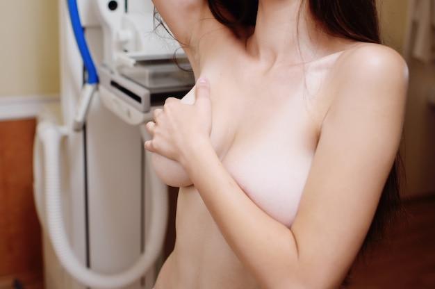 Mulher nova que examina seu peito para protuberâncias ou sinais do cancro da mama.