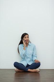 Mulher nova que fala no telefone e sentado no chão