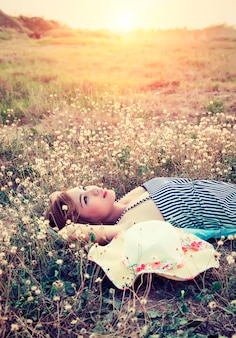 Mulher nova que pensa ao pôr do sol