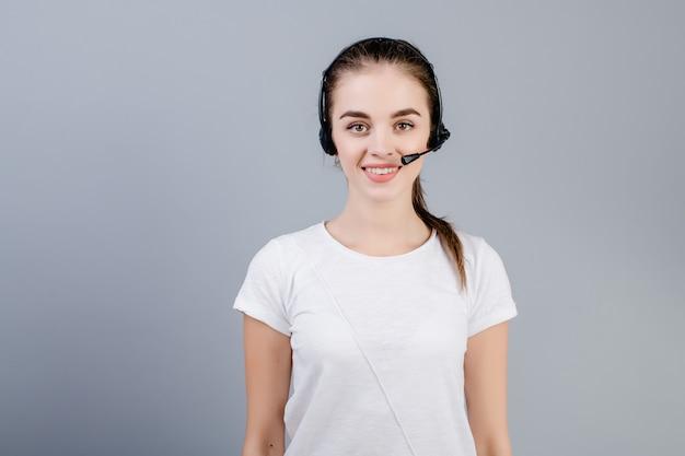 Mulher nova sorridente do despachante do centro de atendimento que veste clientes de resposta isolados sobre o cinza