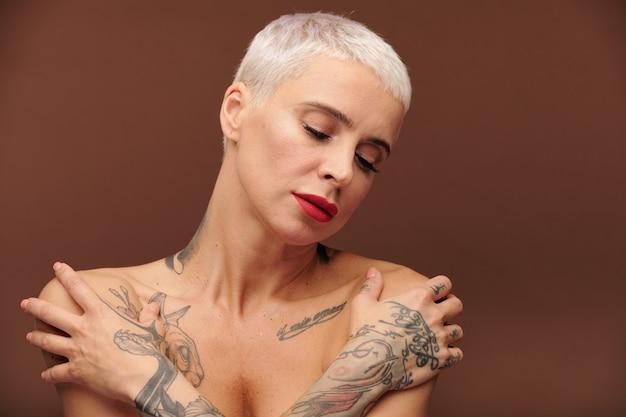 Mulher nua com aparência de homem com tatuagens nas mãos, dedos, ombros e pescoço, mantendo os olhos fechados enquanto fica em pé na frente da câmera, isolado