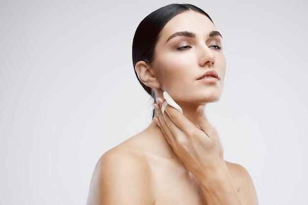 Mulher nua com creme desconectável para cuidados com a pele, close-up