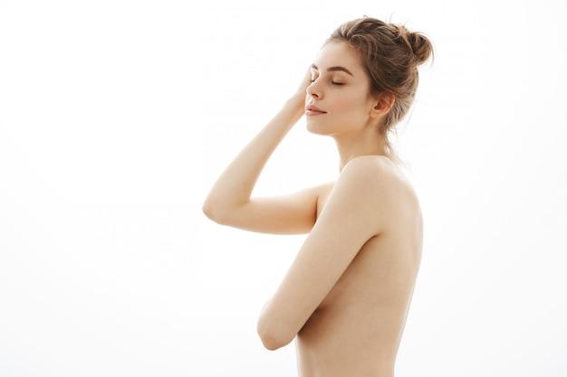 Mulher nua macia jovem com bolo posando sobre fundo branco. olhos fechados. perfil.