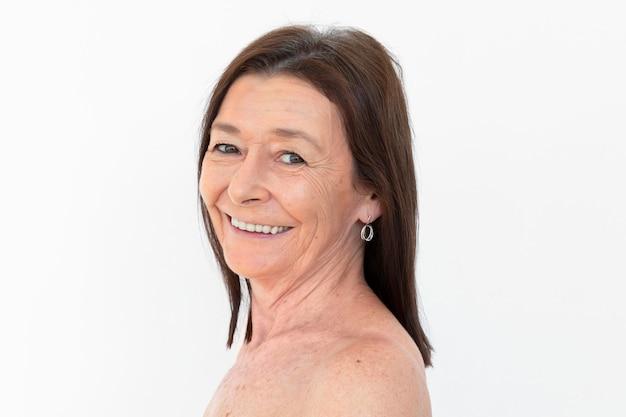 Mulher nua sênior sorrindo para a câmera