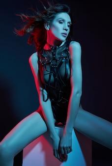 Mulher nua sexy em um cinto na luz de neon. figura perfeita e seios de uma mulher em roupa interior