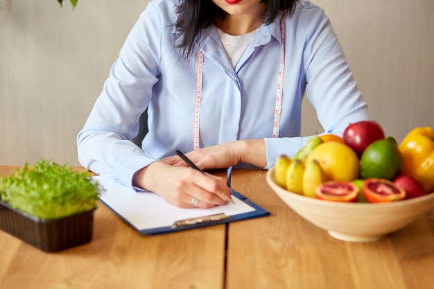 Mulher nutricionista escrevendo um plano de dieta, com frutas e vegetais saudáveis