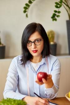 Mulher nutricionista no escritório, segurando maçã na mão