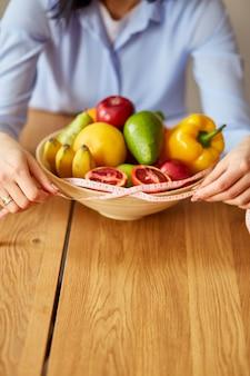 Mulher nutricionista segurando torneira e tigela de medição com frutas e vegetais saudáveis