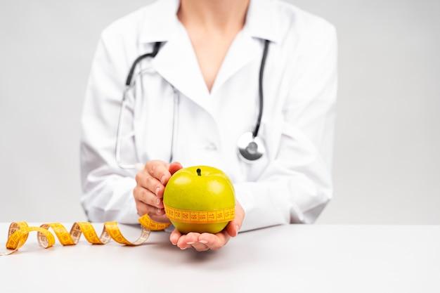 Mulher nutricionista segurando uma maçã