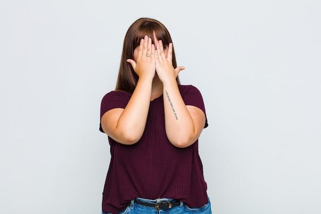 Mulher obesa cobrindo o rosto com as mãos, espiando por entre os dedos com expressão de surpresa e olhando para o lado