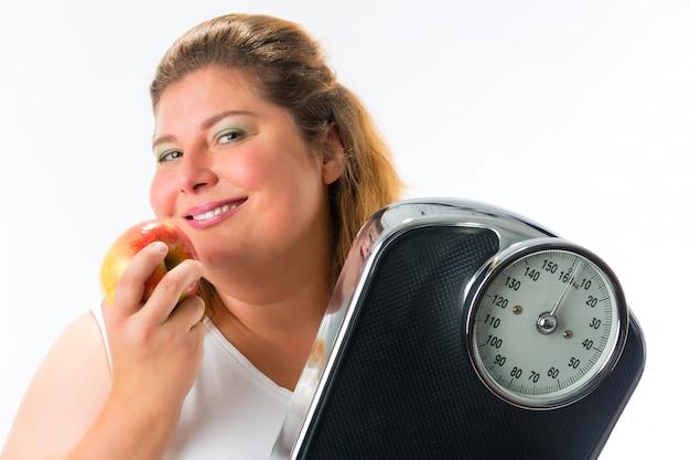 Mulher obesa com escala debaixo do braço e maçã