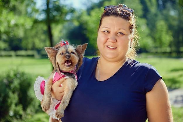 Mulher obesa com yorkshire terrier fêmea nos braços