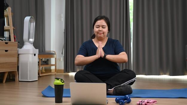Mulher obesa encantadora pratica ioga com o laptop em casa.